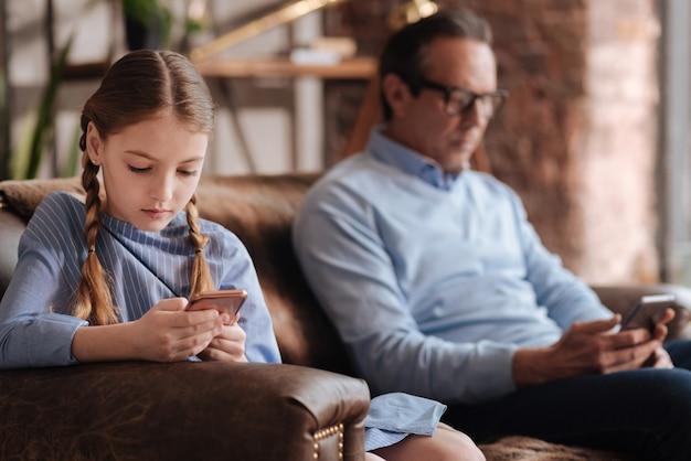 Ragazza giovane apatica dipendente che si siede sul divano e utilizza il cellulare mentre suo nonno naviga in internet