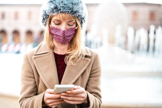 Donna dipendente con maschere protettive utilizzando l'app di monitoraggio sullo smartphone mobile