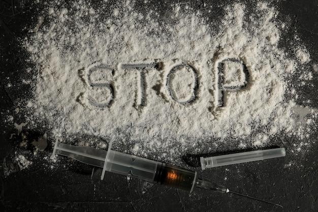 Droghe che creano dipendenza. l'eroina in una siringa e l'iscrizione fermano la cocaina su un tavolo nero. il concetto di tossicodipendenza. vista dall'alto