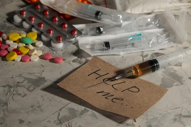 Droghe che creano dipendenza. lsd, cocaina, eroina e la scritta mi aiutano a un tavolo luminoso. il concetto di tossicodipendenza.