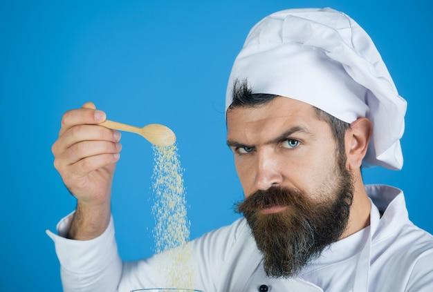 Aggiunta di semole ritratto di chef maschio barbuto che spolvera uomo di semole che spolvera porridge di mais crudo