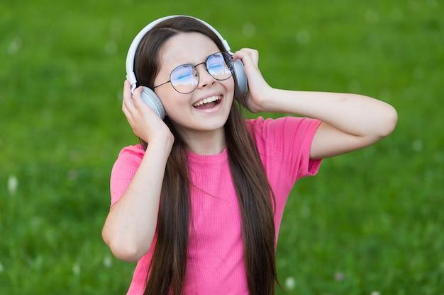 Aggiungere felicità attraverso il canto. il cantante felice canta una canzone sull'erba verde. la bambina si diverte a cantare in cuffia. voce che canta. esercizi vocali. musica estiva. godersi il canto da solista.
