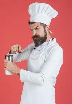 Aggiunta di condimento. lo chef maschio barbuto tiene l'agitatore di sale. uomo barbuto. cucina, professione e concetto di persone. concetto professionale di preparazione del cibo.