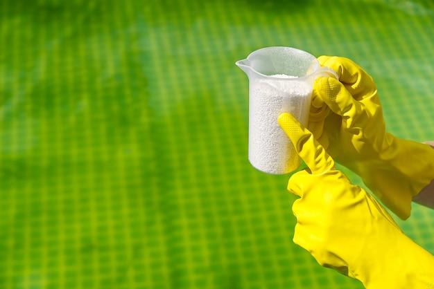Aggiunta di polvere di cloro per la piscina per rimuovere le alghe e disinfettare l'acqua. concetto gonfiabile di cura della piscina.
