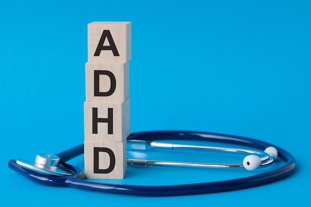 Lettere adhd scritte su blocchi di legno e stetoscopio su superficie azzurra
