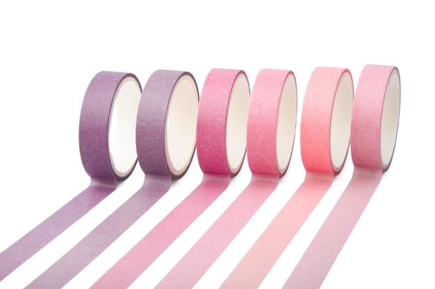 Rotoli di nastro adesivo e strisce parallele isolati su sfondo bianco