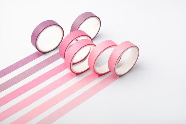 Rotoli di nastro adesivo e strisce parallele su fondo bianco