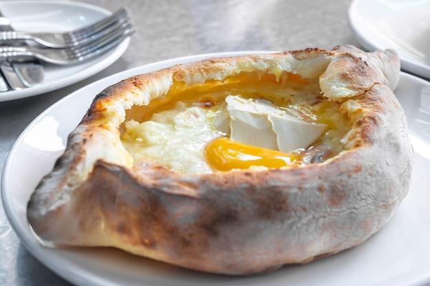 Khachapuri adjarian con uova e burro sul tavolo, cibo