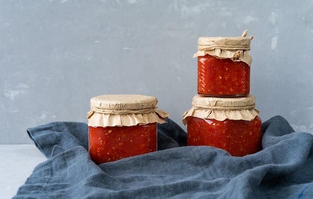 Adjika - condimento aromatico speziato per piatti di carne e pesce su tavola di salsa in tre vasi di vetro. vista laterale, orientamento orizzontale.