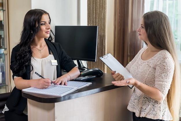 Amministratore e cliente che parlano vicino al tavolo della reception
