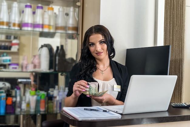 Amministratore che conta le banconote in dollari nel salone di bellezza