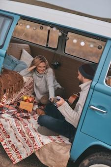 Ammirato dal suo talento. vista dall'alto di un bel giovane che suona la chitarra per la sua bella ragazza mentre è seduto in un mini furgone blu in stile retrò