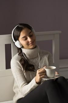 Adolescente sul letto ascoltando musica con le cuffie e la tazza di tè