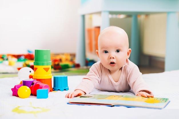 Adorabile bambino di 6 mesi che guarda e legge un libro bambino che gioca con giocattoli colorati a casa
