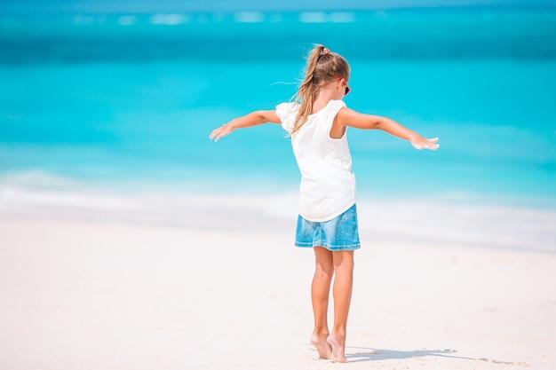 Adorabile bambina attiva in spiaggia durante le vacanze estive