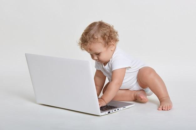 Neonato adorabile che si siede sul pavimento e che guarda lo schermo del laptop