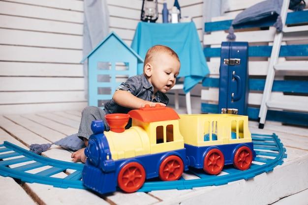 Neonato adorabile che si siede e che gioca con i giocattoli del treno di colore a casa. giocattoli educativi per bambini in età prescolare e asilo nido. parco giochi al coperto.
