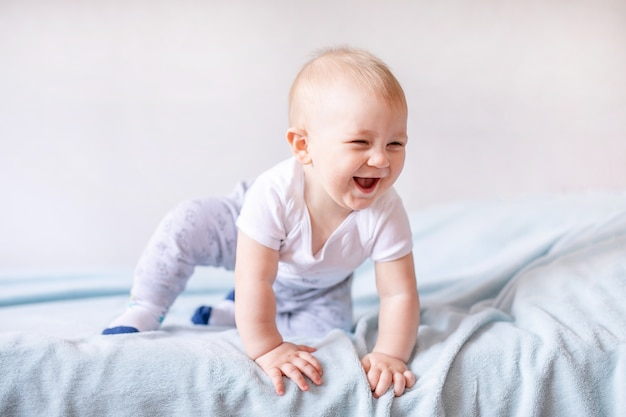 Neonato adorabile in camera da letto soleggiata bianca. neonato che si rilassa su un letto blu. asilo nido per bambini piccoli. Foto Premium