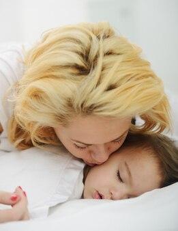 Neonato adorabile con la mamma sul letto