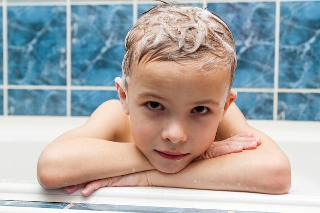 Adorabile bambino con schiuma di sapone shampoo sui capelli facendo il bagno. ritratto del primo piano del concetto sorridente del bambino, di sanità e dell'igiene come logo. isolato su sfondo bianco e blu con tracciato di ritaglio.