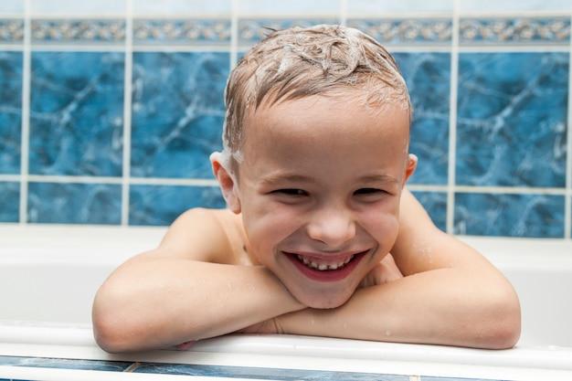 Adorabile bambino con schiuma di sapone shampoo sui capelli facendo il bagno.