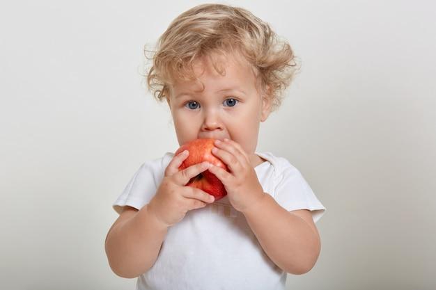 Adorabile bambino che mangia mela rossa isolato su uno spazio bianco, bambino che guarda l'obbiettivo mentre morde la frutta, indossa la maglietta