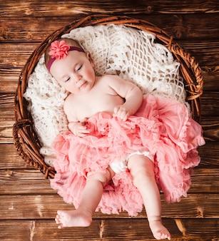 Adorabile bambina in tutù rosa sdraiato nel cestino. fotografia neonato