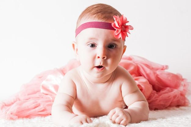 Adorabile bambina in tutù sdraiata sul morbido tappeto