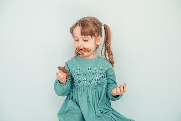 Adorabile bambina con il viso ricoperto di cioccolato.