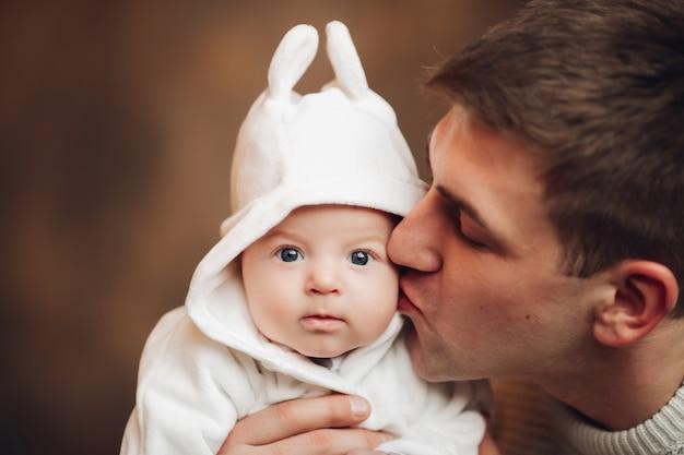 Adorabile bambino che indossa il cappuccio con orecchie da coniglio guardando la parte anteriore con calma