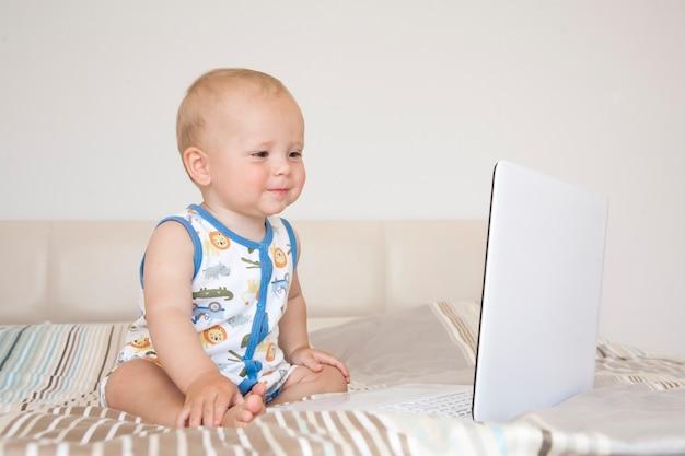 Ragazzo biondo adorabile del bambino che si siede sul letto e che guarda il computer portatile a casa, all'interno. bambino con computer tablet.