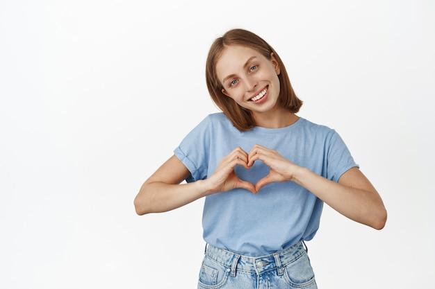 Adorabile donna bionda, sorridente adorabile e mostrando il cuore, ti amo gesto, essendo romantica e simpatica, in piedi con una maglietta blu sul muro bianco