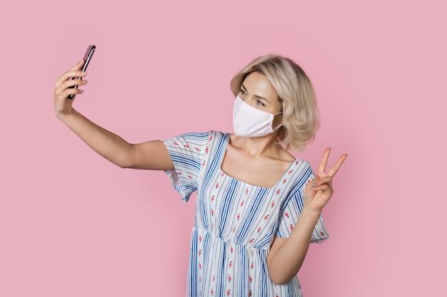 Adorabile signora bionda in mascherina medica nel gesticolare il segno di pace mentre si prende un selfie su una parete rosa