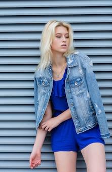 Adorabile modella bionda che indossa abiti di moda in posa vicino alle persiane metalliche in strada