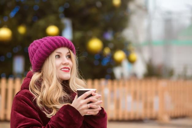 Adorabile donna bionda vestita con abiti invernali e che beve caffè all'albero di natale