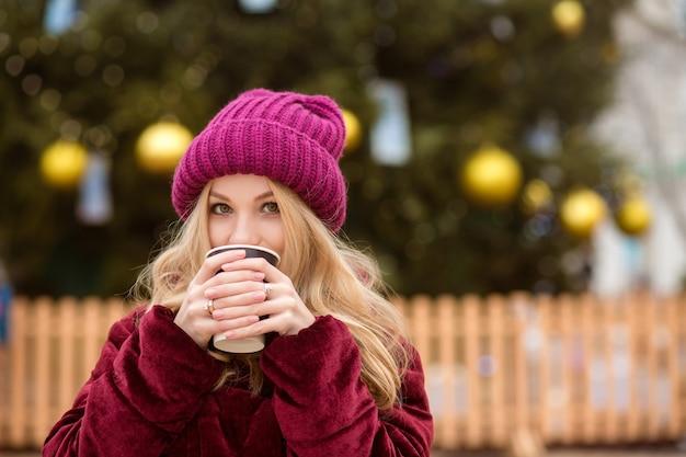 Adorabile donna bionda che beve caffè vicino all'albero di natale nella piazza centrale di kiev