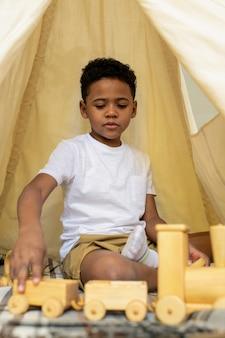 Adorabile ragazzo di età elementare in abbigliamento casual che si siede sul pavimento all'interno della tenda bianca e gioca con il trenino di legno nella scuola materna