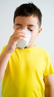 Ragazzo adorabile con un bicchiere di latte o kefir su sfondo bianco