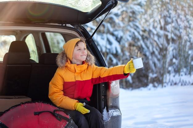 Adorabile ragazzo con tè caldo o cacao nelle sue mani seduto in macchina nera al giorno d'inverno. viaggio su strada, fuga, ambiente naturale, soggiorno, viaggio, turismo in inverno.