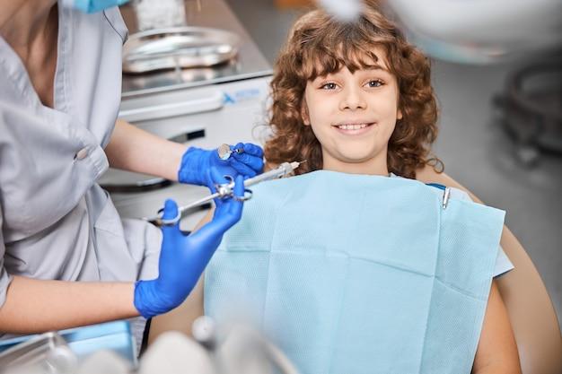 Adorabile ragazzo brunetta seduto su una poltrona odontoiatrica e sorridente dopo aver ricevuto un'iniezione di anestetico da un dentista
