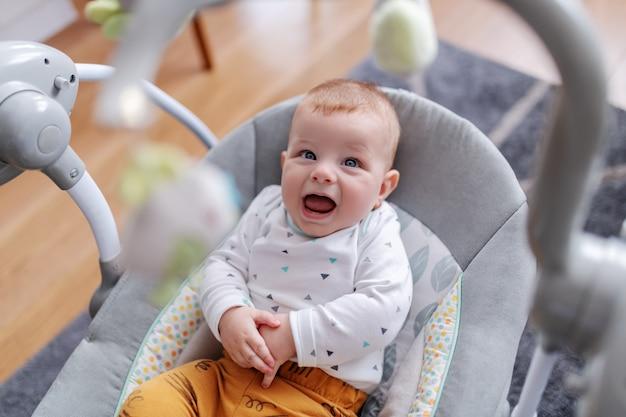 Adorabile bambino caucasico seduto nella sua sedia a dondolo, parlando linguaggio del bambino e guardando i giocattoli.