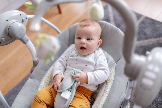 Neonato sorridente caucasico adorabile che si siede nella sua sedia dell'attuatore e che esamina i giocattoli.