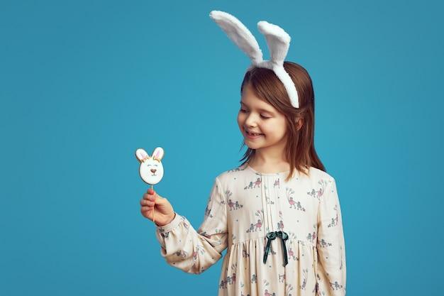 Adorabile ragazza affascinante che sorride e tiene in mano un biscotto a forma di coniglio che indossa orecchie da coniglio sul muro blu