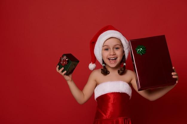 Adorabile bambina allegra in abiti da carnevale di babbo natale, tiene in mano una scatola regalo di natale in carta da imballaggio verde e rossa e gioisce sorridendo alla telecamera in posa su sfondo colorato con spazio copia per annuncio