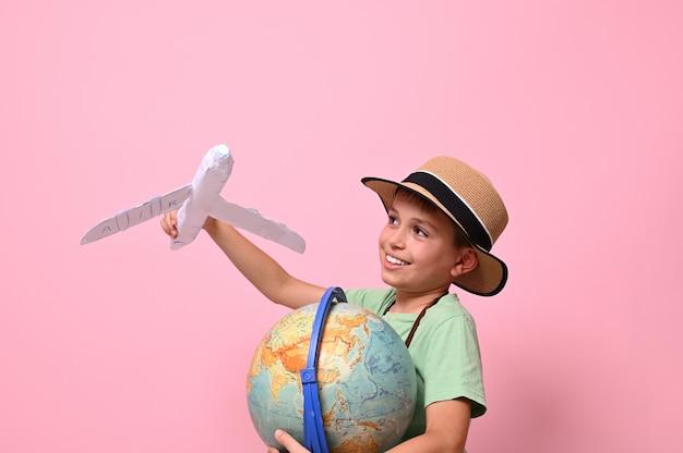 Adorabile bambino gioca con un aeroplano di carta simulando un volo intorno al pianeta terra.