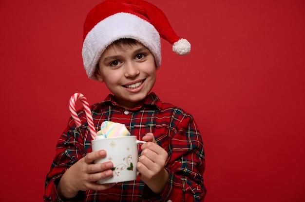 Adorabile bambino con un bel sorriso a trentadue denti, che indossa il cappello di babbo natale e posa su uno sfondo rosso con una tazza di cioccolata calda con marshmallow e zucchero filato dolce a strisce. concetto di natale