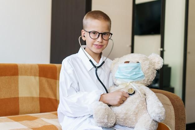 Un adorabile bambino vestito da dottore gioca con un orsacchiotto mentre si controlla il respiro con un...