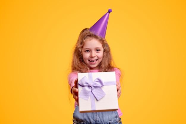 Bambino adorabile in cappello del partito che mostra il contenitore di regalo