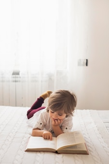 Bambino adorabile che legge la bibbia a casa