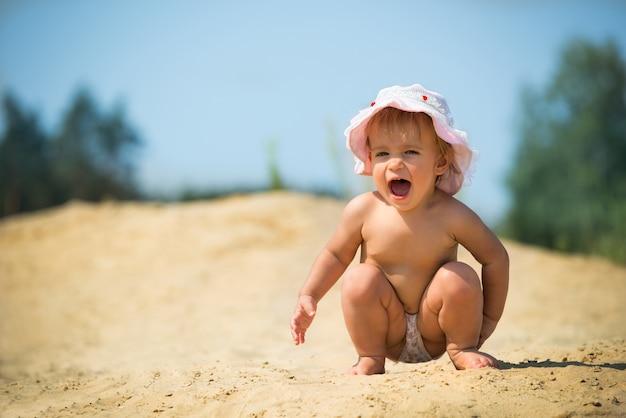 Adorabile bambino, urla e si siede sulla sabbia